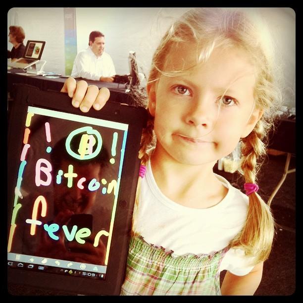 niña con un tablet en el que ha dibujado Bitcoin Fever, su padre se refleja apasionado en el tablet